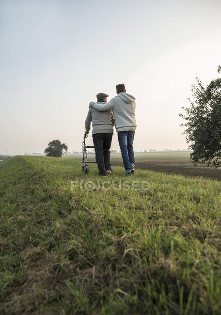 Senior man and grandson in rural landscape with wheeled walker — Stock Photo