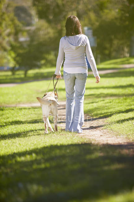 Sehbehinderte Frau zu Fuß mit Blindenhund in einem park — Stockfoto