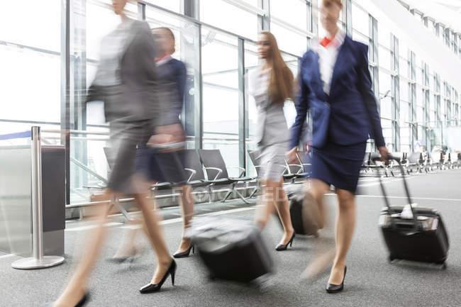 Empresarias y asistentes de vuelo en el aeropuerto - foto de stock