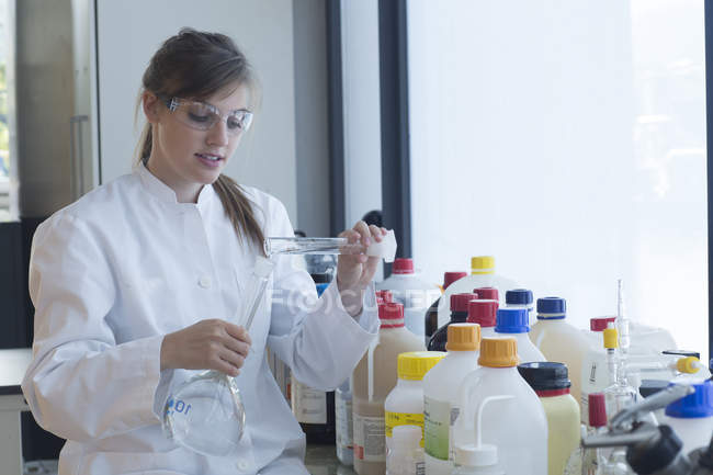 Young female chemist filling liquid in recipient in a chemical laboratory — Stock Photo