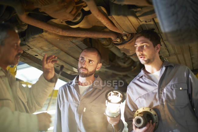 Two car mechanics with client in repair garage — Stock Photo