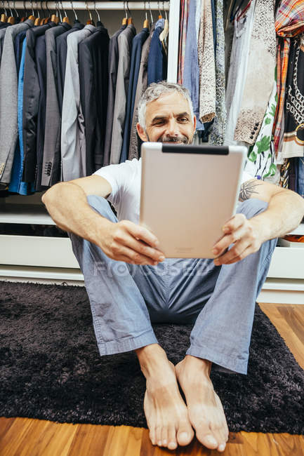Man with his digital tablet sitting on the floor of his walk-in closet — Stock Photo