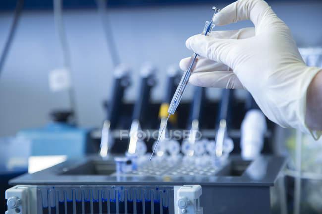 Main avec un gant de protection tenant une seringue au labroratoire de biochimie — Photo de stock