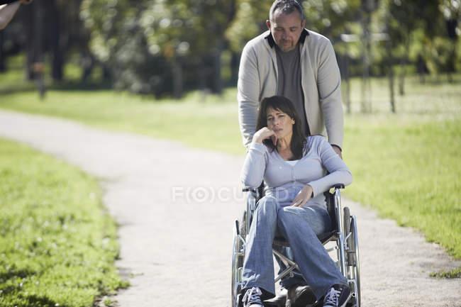 Homme poussant femme en fauteuil roulant dans le parc — Photo de stock