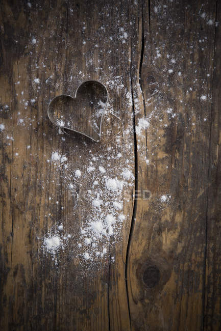 Heart shaped cookie cutter and scattered flour on dark wood — Stock Photo