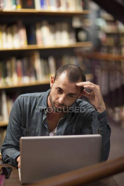 Студент с ноутбуком в библиотеке — стоковое фото