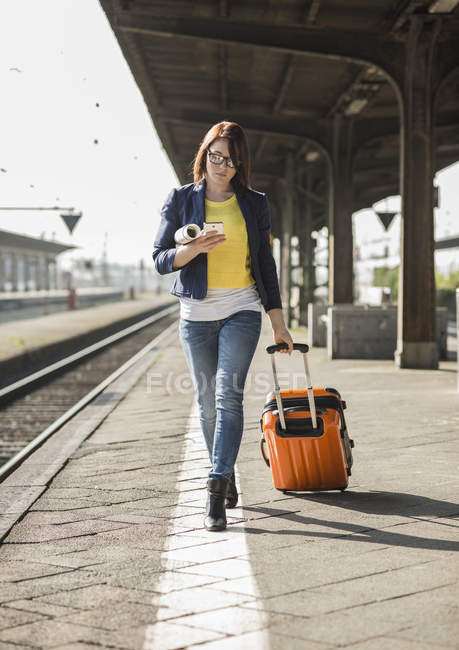 Woman with baggage at train station — Stock Photo