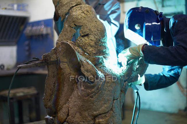 Art foundry worker welding cast parts — Stock Photo