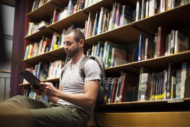 Étudiant utilisant une tablette numérique dans une bibliothèque — Photo de stock