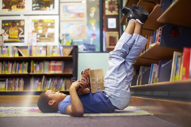 Boy lying on floor in library — Stock Photo