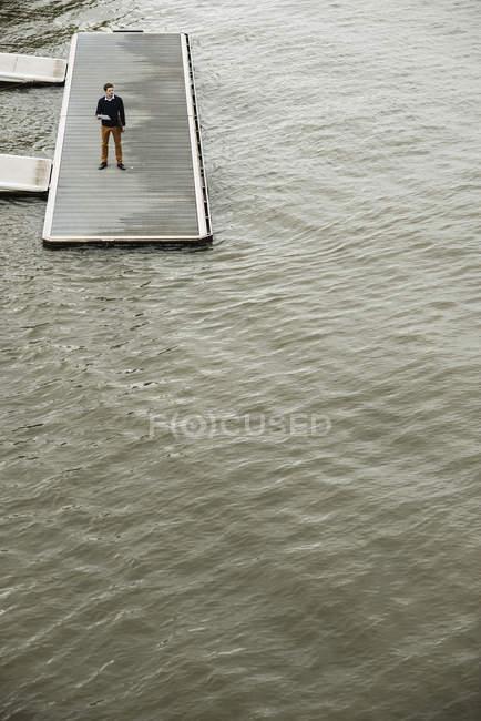 Молодой человек стоит на причале со своим цифровым планшетом — стоковое фото