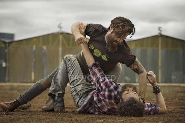 Двое мужчин с полной бороды, боевые действия в заброшенных пейзаж — стоковое фото