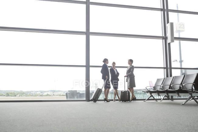 Attentdants de vuelo y a la empresaria en una ventana en el aeropuerto - foto de stock