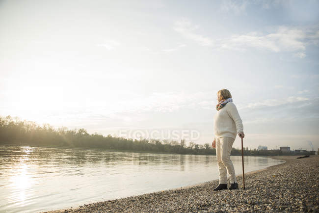 Senior woman with walking stick standing at waterside watching sunset — Stock Photo