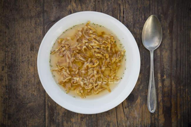 Блюдо из Швабский Flaedle суп и ложка на темное дерево — стоковое фото