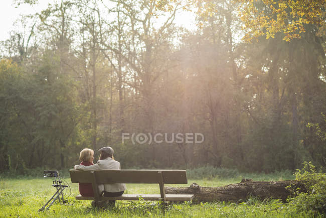 Senior woman and granddaughter sitting on a park bench, back view — Stock Photo