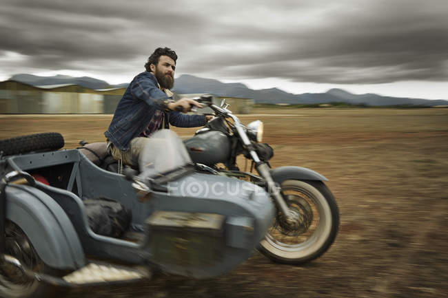Man with full beard driving motorcycle with sidecar — Stock Photo
