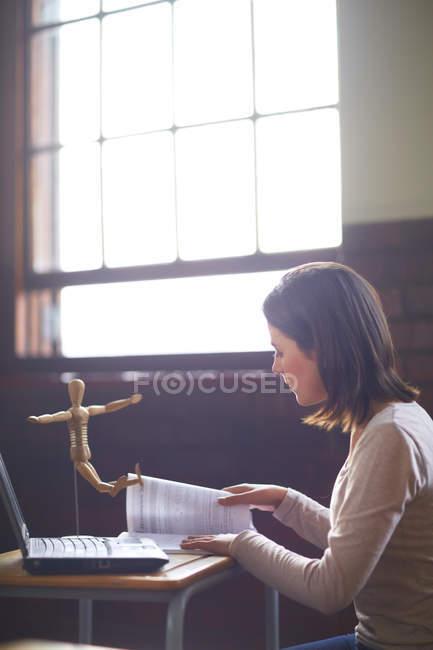 Studentin im Klassenzimmer mit Laptop, Buch und anatomischem Modell — Stockfoto