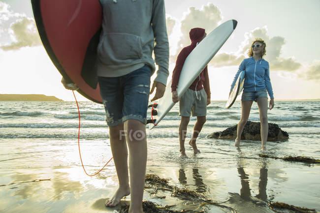 Três adolescentes com pranchas de surf andando à beira-mar — Fotografia de Stock