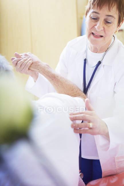 Médico examinando homem sênior na cama do hospital — Fotografia de Stock