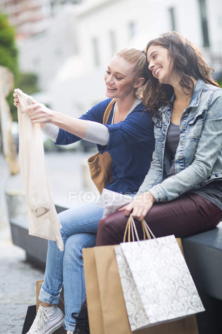 Two female friends watching their purchases — Stock Photo