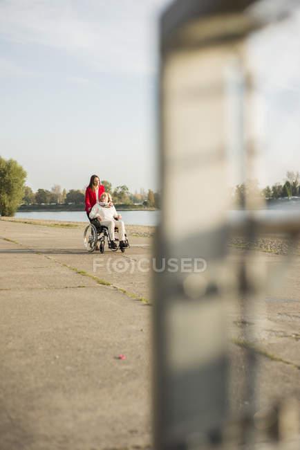 Взрослый внучка, содействие ее бабушка, сидя в инвалидном кресле — стоковое фото