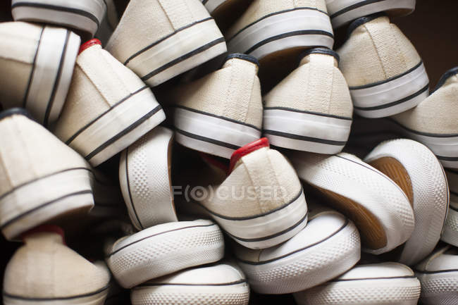 Pile of white canvas shoes — Stock Photo