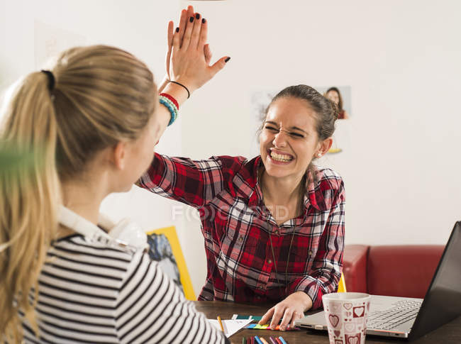 Two happy female friends giving high five at home — Stock Photo
