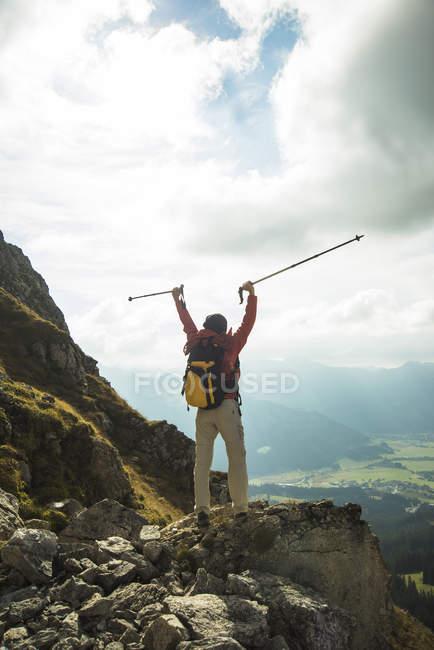Frau jubelt auf Berggipfel — Stockfoto