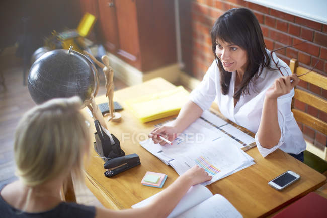 smiling teacher talking to student at desk young woman south