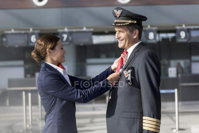 Sonriente azafata ajuste de lazo del piloto en el aeropuerto - foto de stock