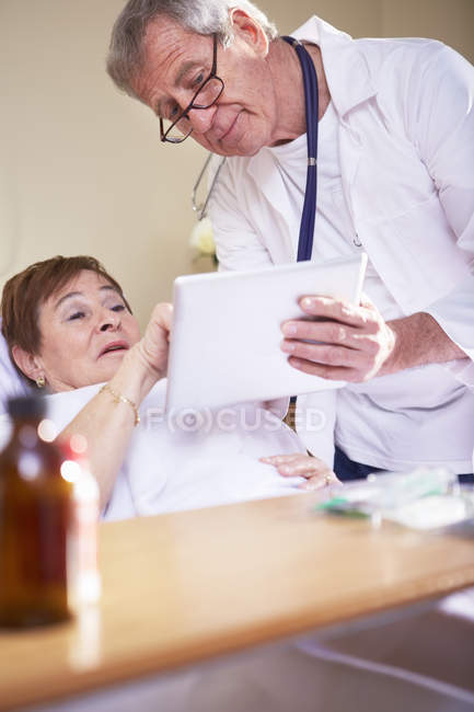 Doctor showing digital tablet to senior woman in hospital bed — Stock Photo