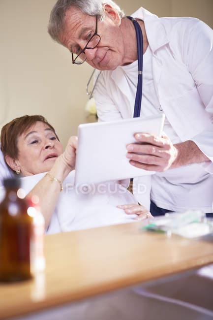 Médico mostrando tablet digital para mulher idosa na cama do hospital — Fotografia de Stock