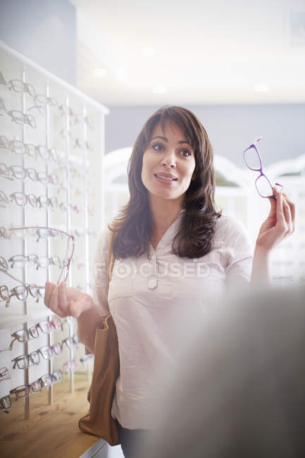 Smiling Woman trying on glasses at optician — Stock Photo