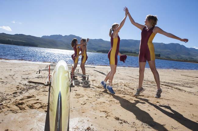 Четыре женщины гребут на берегу озера — стоковое фото