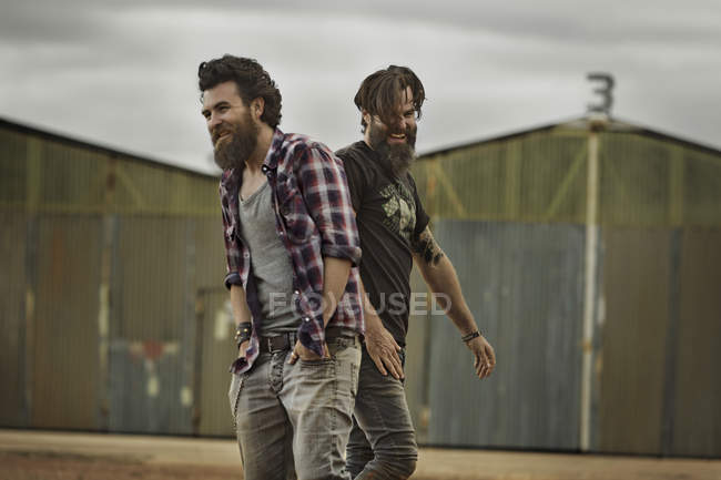 Two smiling men with full beards in abandoned landscape — Stock Photo