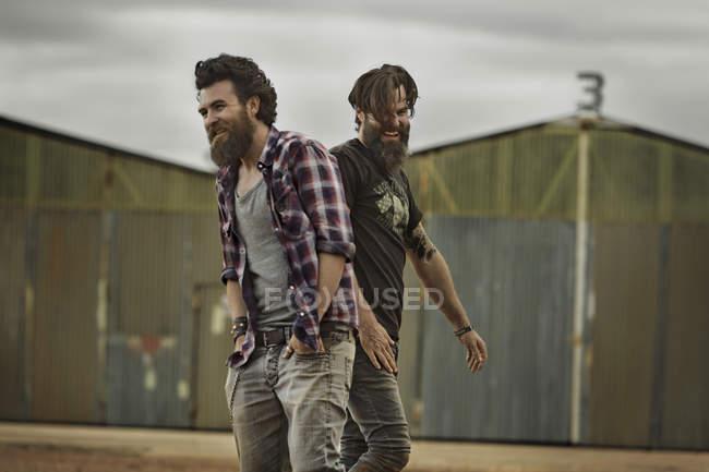 Два усміхнений чоловіків з повного бородами в занедбані краєвид — стокове фото