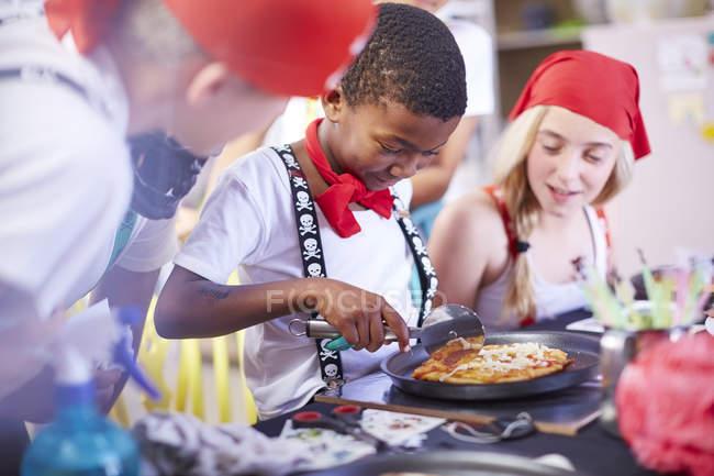 Дети, одетые как пираты, едят пиццу на вечеринке — стоковое фото