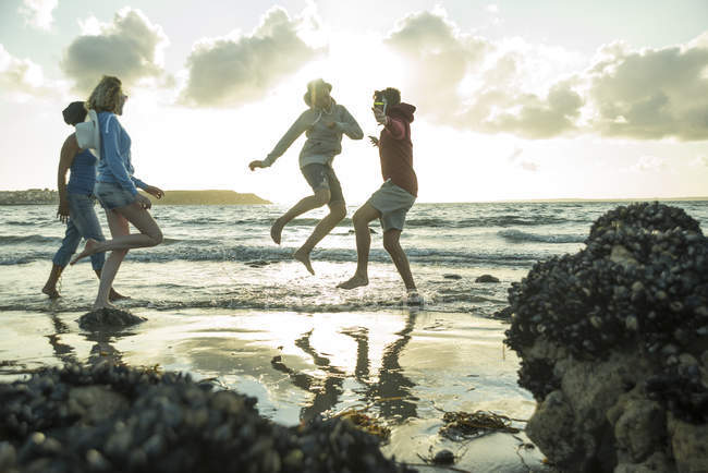 Woman and three teenagers having fun on the beach by sunset — Stock Photo
