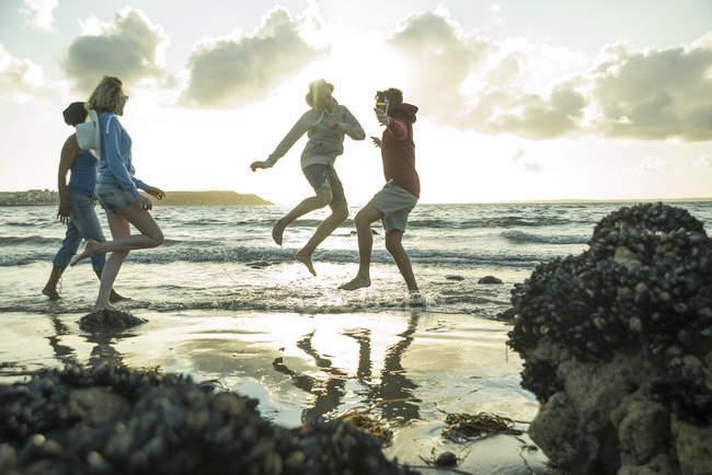 Женщина и трое подростков веселятся на пляже к закату — стоковое фото
