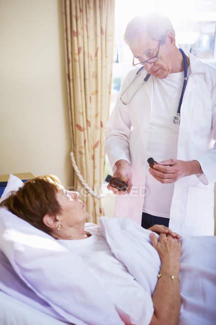 Doutor falando com a mulher sênior deitada na cama do hospital — Fotografia de Stock