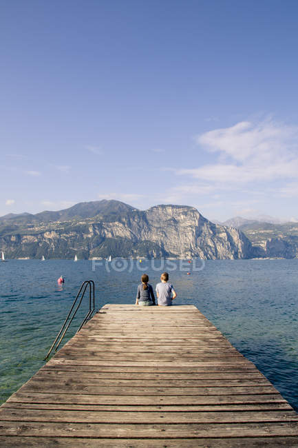 Italy, Veneto, Malcesine, Brother and sister sitting on jetty — Stock Photo
