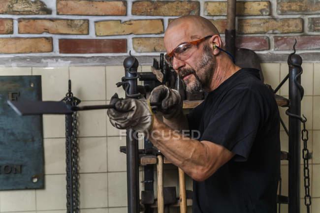 Knife maker examining work piece in workshop — Stock Photo