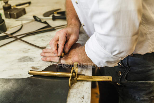 Saddler cutting leather with strap cutter — Stock Photo