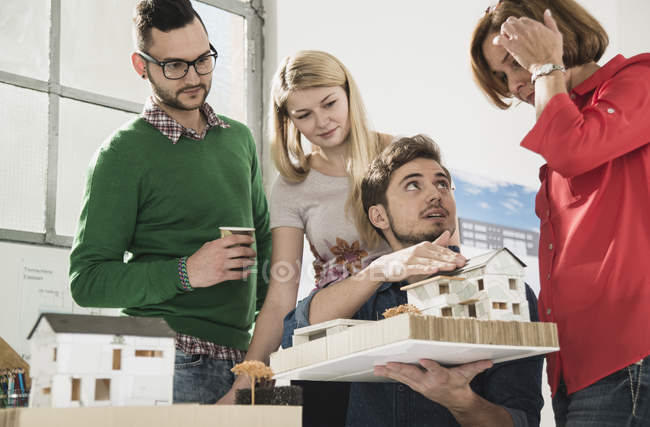 Group of architects in office with architectural model — Stock Photo