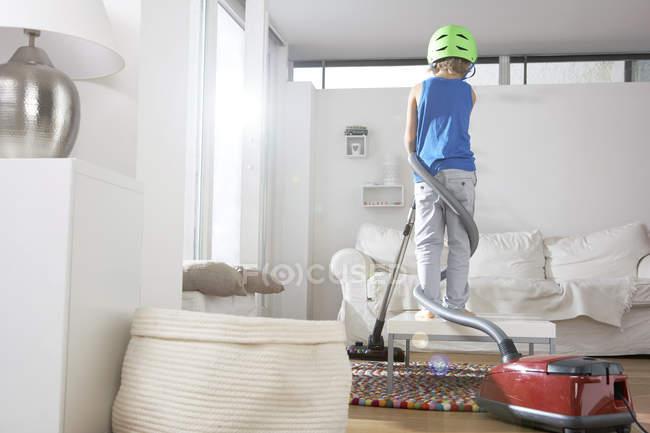 Garçon dans le salon empêtré dans l'aspirateur — Photo de stock