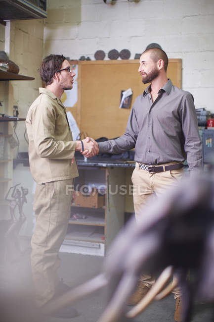 Two men in a sculptor's workshop shaking hands — Stock Photo
