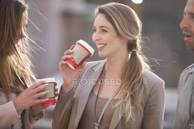Портрет улыбающейся деловой женщины, общающейся со своими коллегами, держащей чашку кофе — стоковое фото