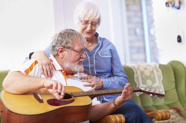 Senior man with wife at home playing guitar — Stock Photo