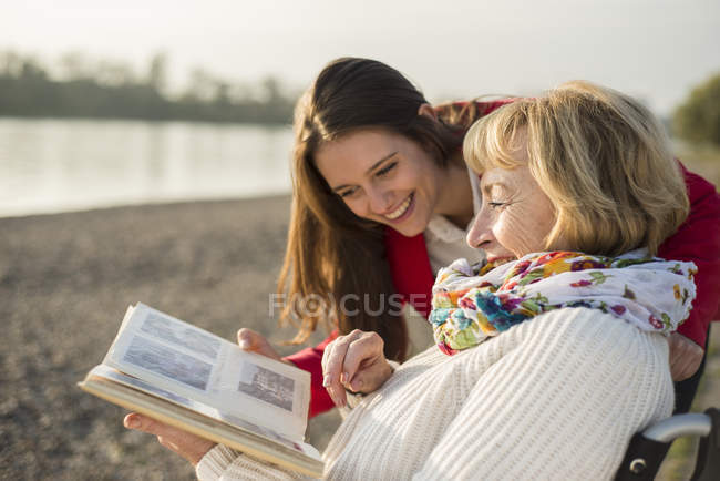 Granddaughter and grandmother watching photo album outdoor — Stock Photo